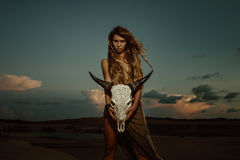 Woman shaman hold cow skull. Portrait of woman with long dreadlocks hair hold in hand staff with cow skull with horn against sunset Stock Photography