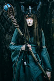 Woman-shaman with horns. In green dress walk in forest stock image