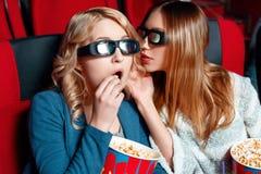 Woman sharing secret in cinema Stock Photo
