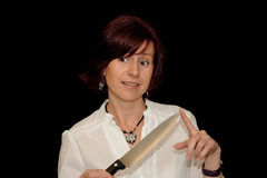 Woman with a sharp knife. A woman holds a sharp knife with her finger on the tip stock image