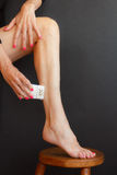 A woman shaves her legs on the stool with the epilator Royalty Free Stock Images