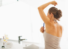 Woman shaving armpit in bathroom Stock Images