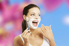 Woman shaving face Stock Photos