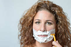 Woman shaving her beard Royalty Free Stock Images