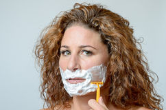 Woman shaving her beard. Close up Serious Face of a Blond middleaged Woman shaving her beard, Staring at the Camera royalty free stock images