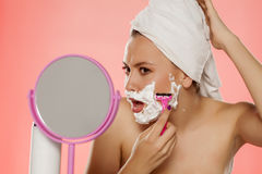 Woman shaving her face. Beautiful young woman shaving her face using foam and a razor royalty free stock image