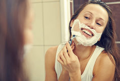 Woman shaving her face Stock Image