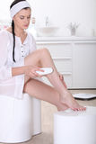 Woman shaving her leg Royalty Free Stock Photography