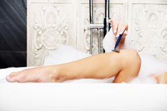 Woman shaving her leg. Royalty Free Stock Photos