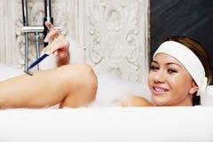 Woman shaving her leg. Royalty Free Stock Image