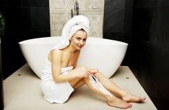 Woman shaving her leg. Stock Image