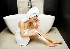 Woman shaving her leg. Stock Photos