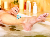 Woman shaving her legs. Young woman shaving her legs in bath stock photography