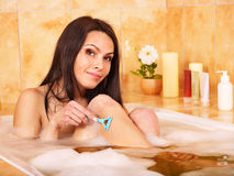Woman shaving her legs Stock Images