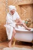 Woman shaving her legs in bathroom. royalty free stock photos