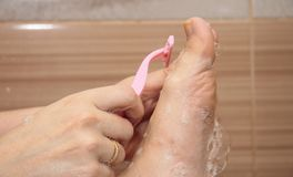 Woman shaving her legs in the bathroom closeup Royalty Free Stock Photo