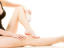 Woman shaving her legs with electric razor. Depilation, epilation, hygiene concept. Woman shaving her legs with electric shaver depilator wearing black swimsuit stock photos