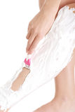 Woman is shaving her legs with foam and razor. Royalty Free Stock Photography