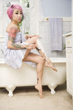 Woman shaving her legs on the side of the bathtub Royalty Free Stock Images