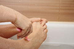 Woman shaving her legs sitting in the bathroom Stock Image