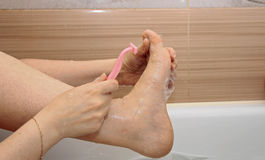 Woman shaving her legs sitting in the bathroom Stock Photography