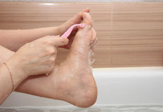 Woman shaving her legs sitting in the bathroom Royalty Free Stock Photos