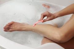 Woman shaving her legs Stock Images