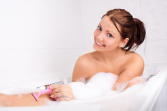 Woman shaving legs Royalty Free Stock Photos