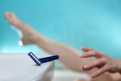 Woman shaving legs. A young woman is reaching for the razor to shave her legs Royalty Free Stock Photos