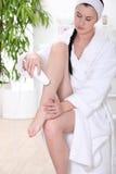 Woman shaving legs Stock Images