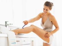 Woman shaving legs in bathroom Royalty Free Stock Images