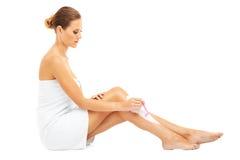 Woman shaving legs Stock Photos