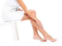 Woman shaving legs. A picture of a sensual woman shaving legs over white background royalty free stock image