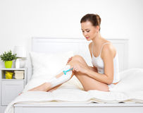 Woman shaving legs with razor. Beautiful young woman shaving legs with razor sits on the bed in bedroom Royalty Free Stock Photos