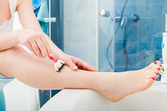 Woman shaving legs with razor in bathroom Stock Images