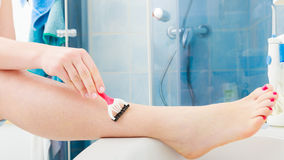 Woman shaving legs with razor in bathroom. Hygiene skin body care concept. Hair removal. Closeup woman shaving legs with razor blade in bathroom Royalty Free Stock Photos