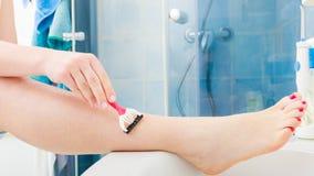 Woman shaving legs with razor in bathroom Royalty Free Stock Photos