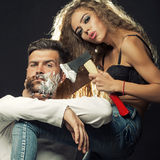 Woman shaving man. Portrait closeup couple of long-haired young sensual women shaving handsome bearded grey-haired men with chopper and foam looking forward on Royalty Free Stock Photo