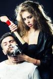 Woman shaving man Royalty Free Stock Image