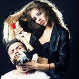 Woman shaving man Stock Image