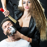 Woman shaving man. Portrait closeup couple of long-haired young sensual women shaving handsome bearded grey-haired men with chopper and foam looking forward on royalty free stock photos