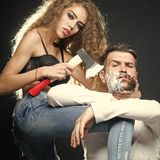 Woman shaving man. Portrait closeup couple of long-haired young sensual women shaving handsome bearded grey-haired men with chopper and foam looking forward on royalty free stock images