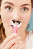 Woman shaving mustache with razor shaver. Hygiene. Stock Image