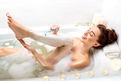 Woman shaving. Young and positive woman shaving her legs in the bath with foam and candles Royalty Free Stock Images