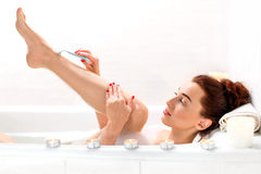 Woman shaving. Young and positive woman shaving her legs in the bath with foam and candles stock photo