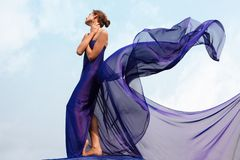 Woman in shawl. Photo of graceful female folded in dark blue chiffon shawl with cloudy sky at background Royalty Free Stock Photos