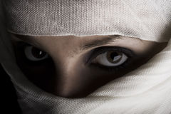 Woman with shawl on face. Young woman with face covered by white shawl and shadow Stock Images