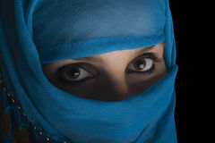 Woman with shawl on face. Young woman with face covered by blue shawl and shadow Royalty Free Stock Images
