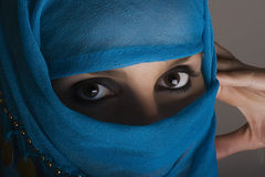 Woman with shawl on face. Young woman with face covered by blue shawl and shadow Stock Image