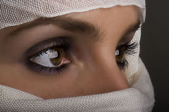 Woman with shawl on face. Young woman with face covered by white shawl and shadow Royalty Free Stock Photos